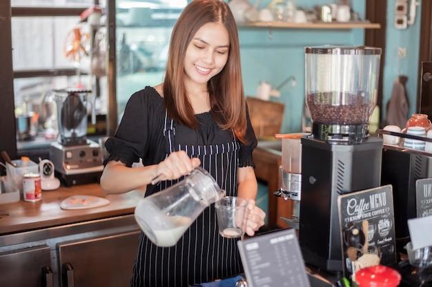 Il bellissimo barista sorride nella sua caffetteria Foto Premium
