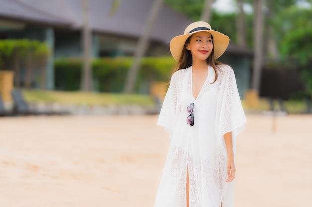 Il bello giovane giovane sorriso asiatico della donna del ritratto felice si rilassa sull'oceano del mare della spiaggia Foto Gratuite