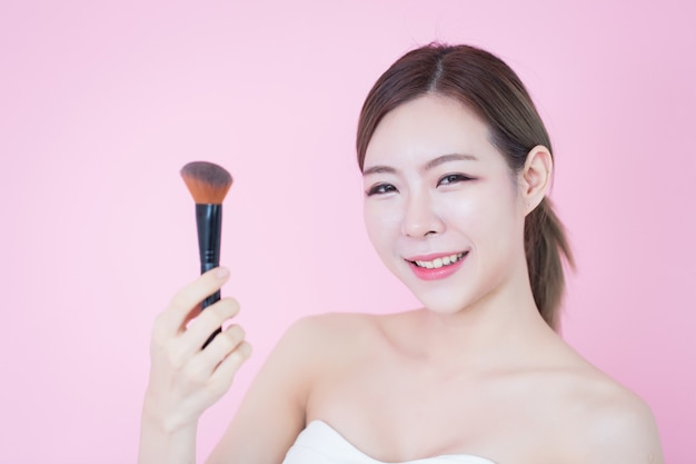 Il bello giovane sorriso asiatico caucasico della donna che applica la spazzola cosmetica spolverizza il trucco naturale. cosmetologia, cura della pelle, pulizia della faccia Foto Premium