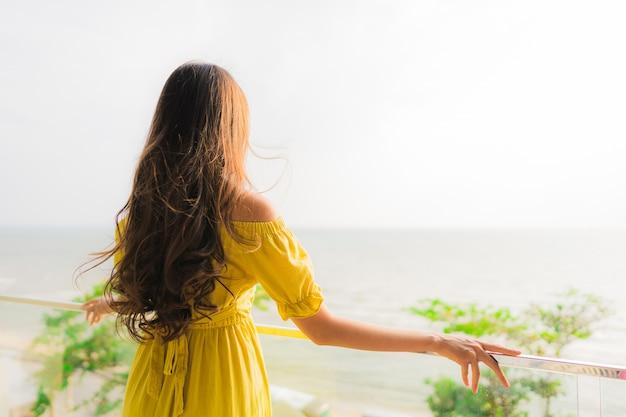 Il bello giovane sorriso asiatico della donna del ritratto felice e si rilassa al balcone all'aperto con la spiaggia e l'oce del mare Foto Gratuite