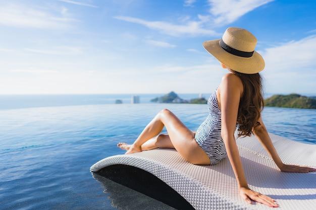 Il bello giovane sorriso asiatico della donna del ritratto felice si rilassa intorno alla piscina nella località di soggiorno dell'hotel per svago Foto Gratuite