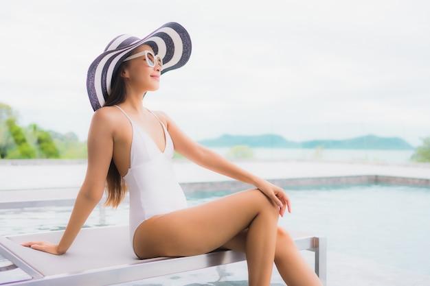 Il bello giovane sorriso asiatico della donna del ritratto si rilassa e svago intorno alla piscina all'aperto Foto Gratuite