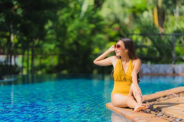 Il bello giovane svago asiatico della donna del ritratto si rilassa sorriso e felice intorno alla piscina nella località di soggiorno dell'hotel Foto Gratuite