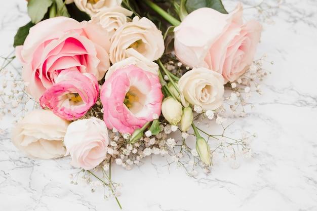 Il bello mazzo fresco del fiore su marmo ha strutturato la priorità bassa Foto Gratuite