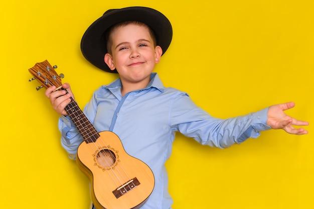 Il bello ragazzino sveglio in cappello e camicia mantiene la chitarra isolata su giallo Foto Premium