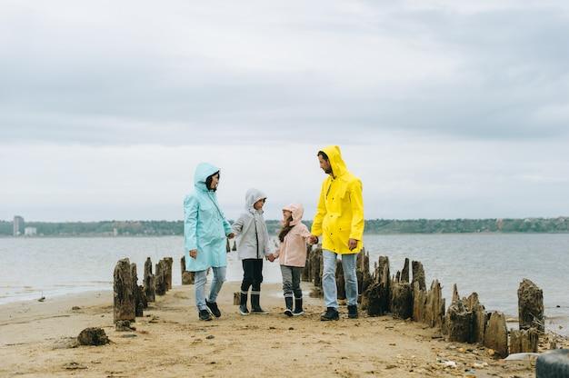 Il bello ritratto della famiglia si è vestito in impermeabile variopinto vicino al lago Foto Premium