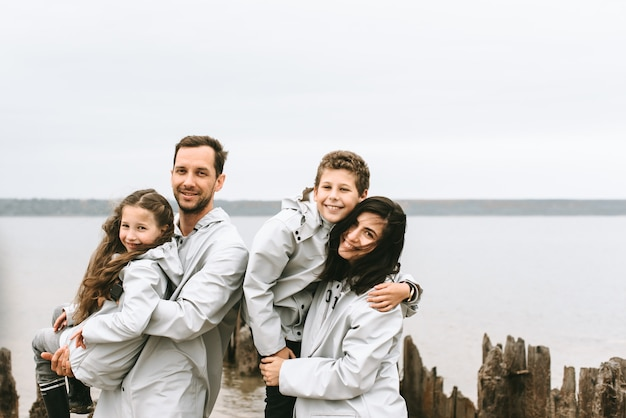 Il bello ritratto di famiglia si è vestito in raincoatnear il mare Foto Premium