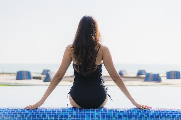 Il bello sorriso felice della giovane donna asiatica e si rilassa nella piscina Foto Gratuite