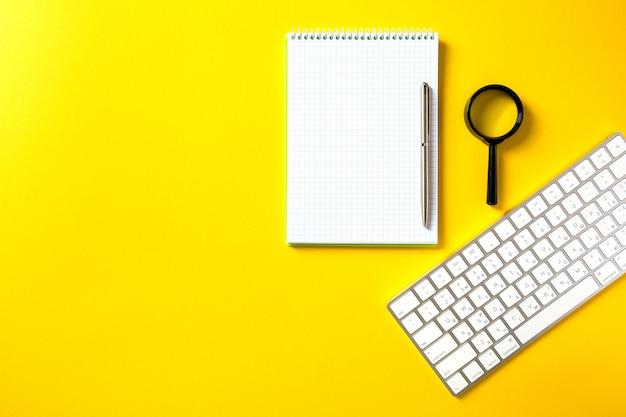 Il blocco note aperto bianco e la tastiera del computer isolata su giallo Foto Premium