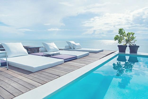 il bordo piscina di lusso con sedie a sdraio bianche sulla