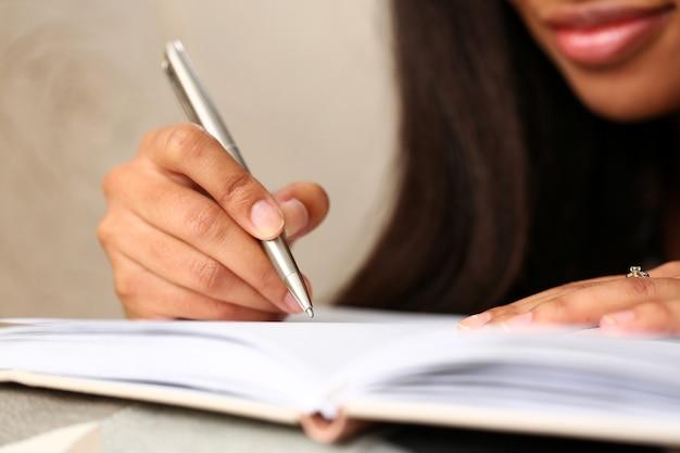 Il braccio della donna di colore scrive la storia in taccuino Foto Premium