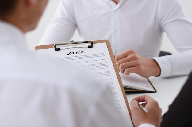 Il braccio maschile in camicia offre una forma di contratto negli appunti Foto Premium