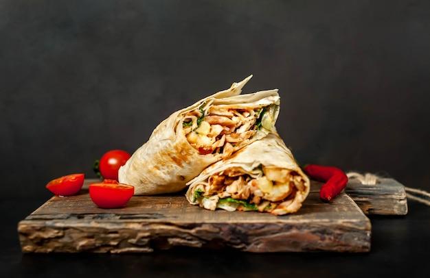 Il burrito si avvolge con pollo e verdure su un tagliere, su uno sfondo di cemento, shawarma messicano Foto Premium