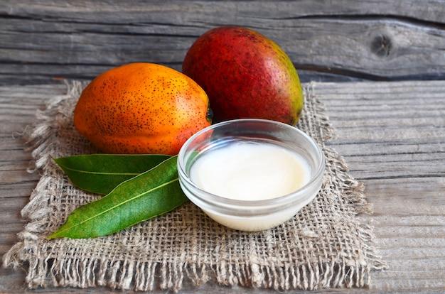Il burro per il corpo del mango in una ciotola di vetro e il mango organico maturo fresco fruttifica su vecchio legno Foto Premium
