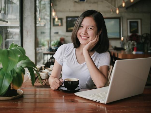 Il caffè bevente della donna asiatica e si rilassa nel caffè della caffetteria Foto Premium