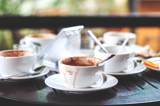Il caffè caldo in una tazza si beve sul tavolo con il soft focus e la luce sullo sfondo Foto Premium