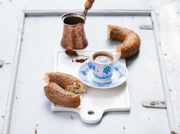 Il caffè nero turco è servito in tazza ceramica tradizionale con il modello, bagel del sesamo chiamato simit sul bordo bianco del servizio sopra la tavola di legno blu-chiaro Foto Premium