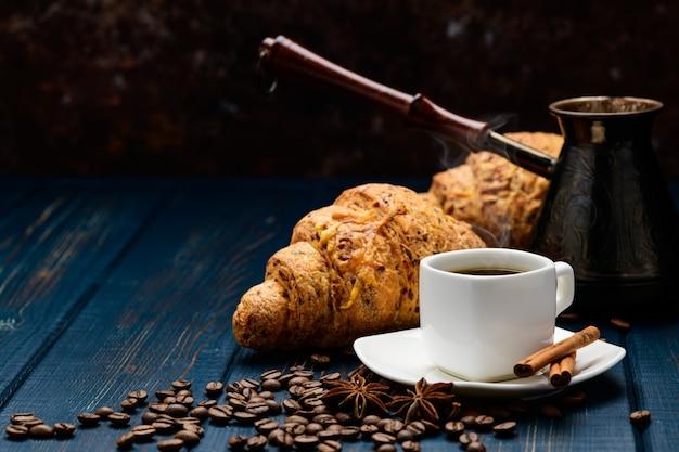 Il caffè si versa in una tazza su un tavolo di legno blu con chicchi di caffè e un cornetto Foto Premium