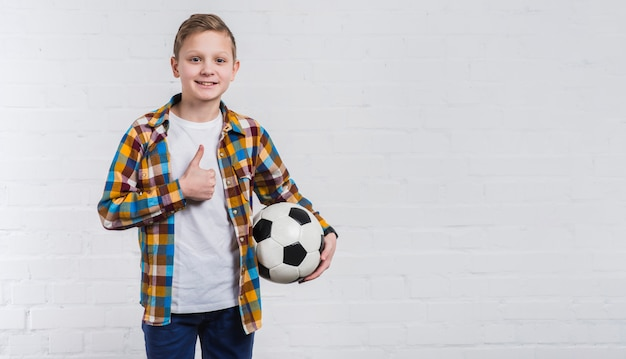 Il calcio sorridente della tenuta del ragazzo a disposizione che mostra il pollice sul segno che sta contro il muro di mattoni bianco Foto Gratuite