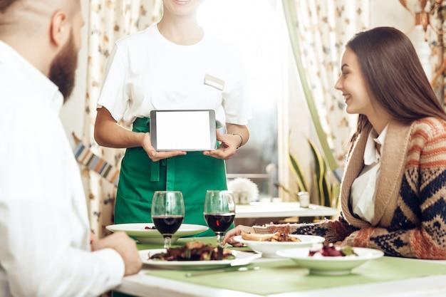 Il cameriere della ragazza prende un ordine da una giovane coppia Foto Premium