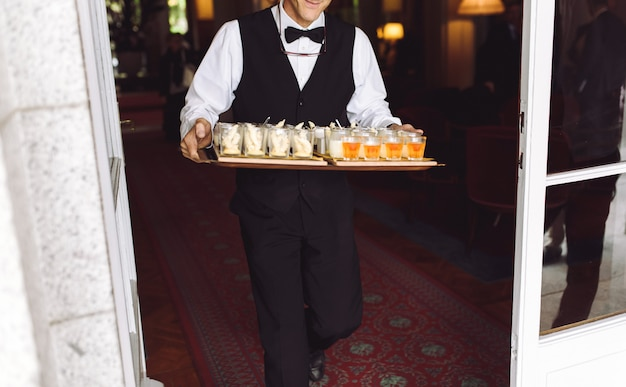 Il cameriere porta il piatto con gli spuntini che camminano al cortile Foto Gratuite