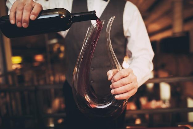 Il cameriere versa il vino rosso dalla bottiglia nel decanter. Foto Premium