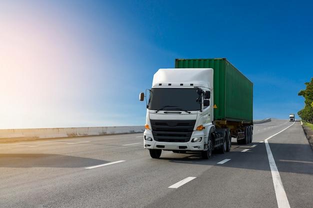 Il camion bianco sulla strada della strada principale con il contenitore verde, importa, trasporta il trasporto logistico Foto Premium
