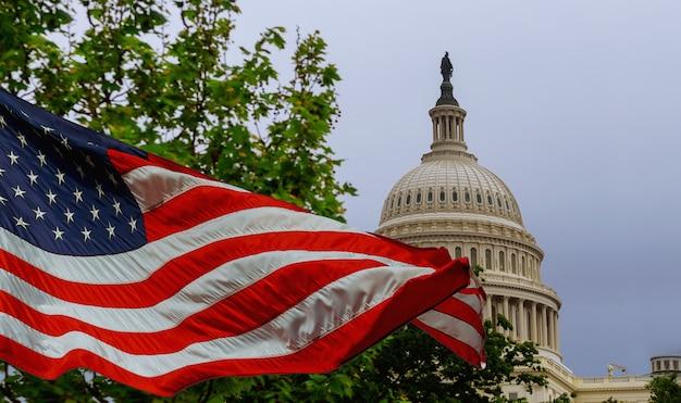 Il campidoglio degli stati uniti che costruisce con una bandiera americana ondeggiante sovrapposta al cielo Foto Premium