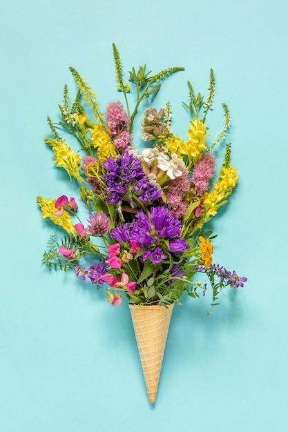 Il campo del mazzo ha colorato i fiori nel cono gelato della cialda sul fondo della carta blu Foto Premium