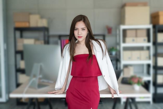 Il capo indossa un vestito rosso e un abito bianco. è sicura che lavora donna e bella. Foto Premium