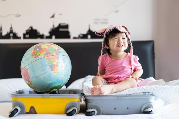 Il cappello d'uso della piccola neonata sveglia asiatica che si siede sulla borsa di viaggio con il sorriso che si sente divertente e che ride sul letto in camera da letto con il globo del mondo ha messo dall'altro lato della borsa della valigia. Foto Premium