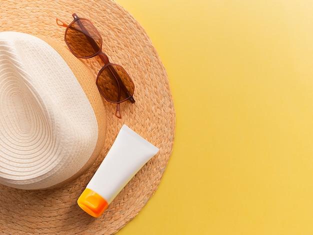 Il cappello della donna della paglia con i vetri di sole e la protezione superiore della crema osservano il fondo giallo luminoso piano. Foto Premium