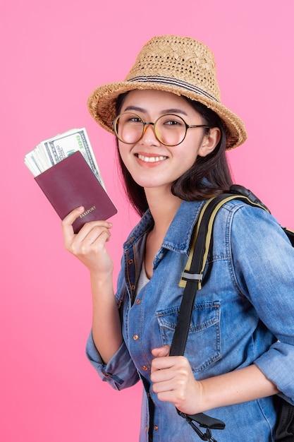 Il cappello di paglia da portare del viaggiatore della donna sta tenendo il passaporto con la banconota Foto Gratuite