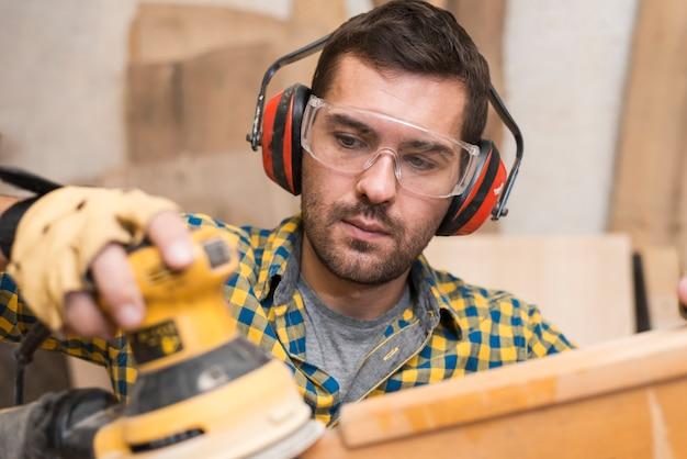 Il carpentiere del costruttore dell'uomo lucida il bordo di legno con una levigatrice orbitale casuale Foto Gratuite