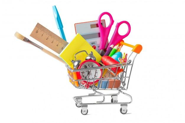 Il carrello della spesa ha riempito di rifornimenti di scuola multicolori isolati su bianco Foto Premium