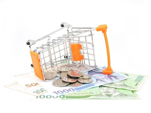 Il carrello di acquisto ha riempito di banconote e monete isolate su fondo bianco. concetto di acquisto Foto Premium