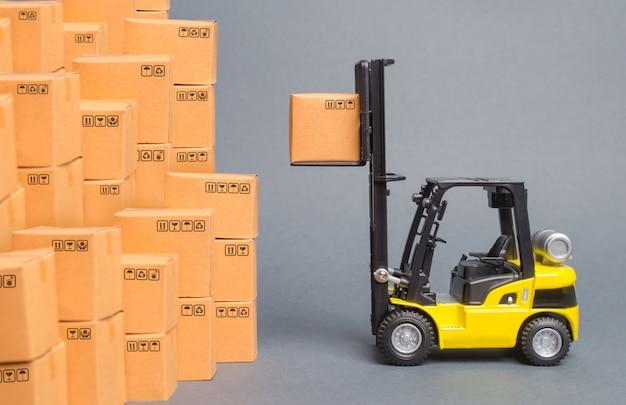 Il carrello elevatore a forcale giallo preleva una scatola su una pila di scatole. servizio di deposito di merci in un magazzino Foto Premium
