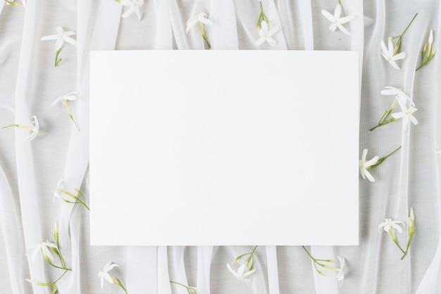 Il cartello bianco di nozze circondato con jasminum auriculatum fiorisce sulla sciarpa Foto Gratuite
