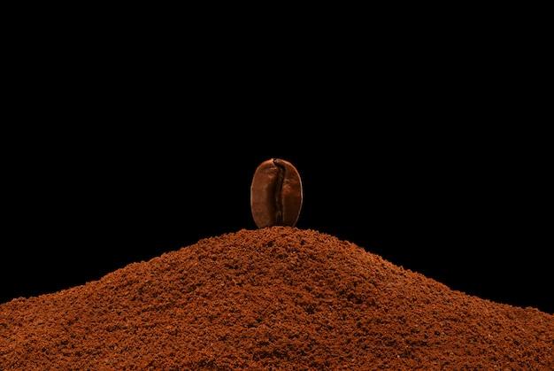 Il chicco di caffè di recente arrostito sta su una dispersione di caffè macinato su un fondo nero Foto Premium