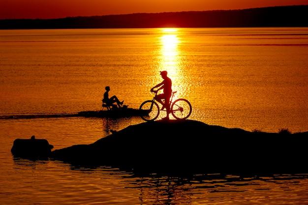Il ciclista maschio sta stando accanto alla sua bici vicino al fiume al tramonto Foto Premium