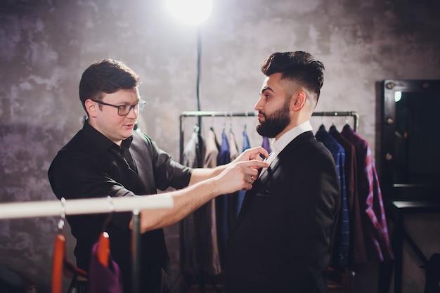 Il cliente maschio al centro commerciale che prova i vestiti di affari con l'aiuto del commesso Foto Premium