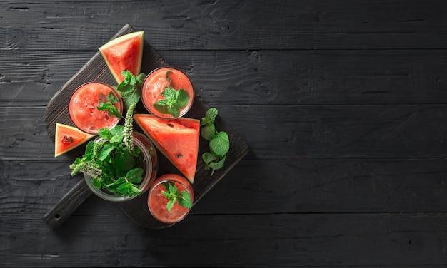 Il cocktail beve il mojito dell'anguria su una tavola di legno scura Foto Premium