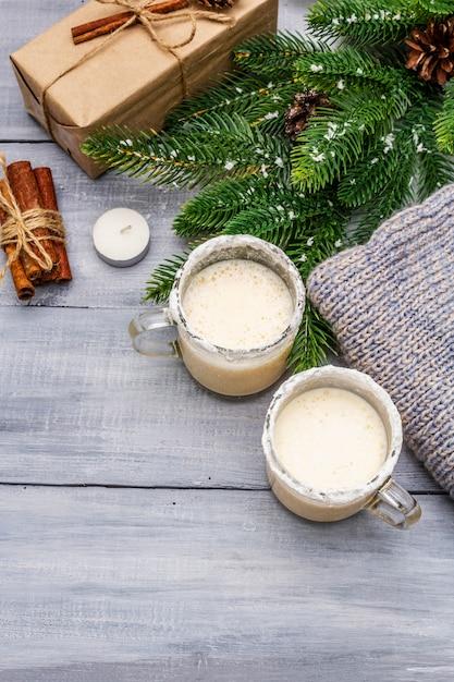 Il cocktail dello zabaione in una tazza di due vetri ha sistemato con la decorazione di natale sulla tavola di legno leggera. ramo di abete sempreverde, regalo, maglia accogliente, neve artificiale Foto Premium
