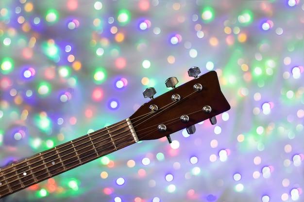 Il collo della chitarra acustica sul fondo del bokeh della luce di natale Foto Premium