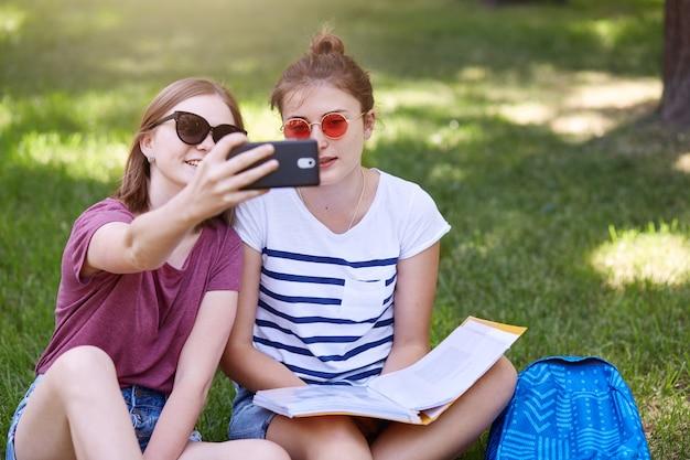 Il colpo all'aperto di due giovani belle femmine che si siedono sull'erba nella posizione di loto, fa il selfie in parco, indossa le magliette e gli shorts, gli occhiali da sole, trascorre il tempo nell'iarda nella calda giornata estiva. Foto Premium