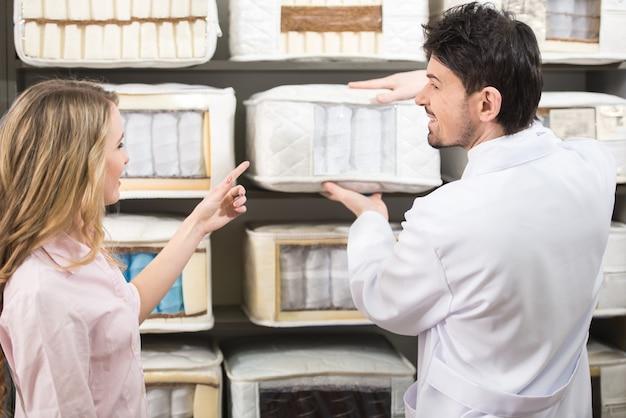 Il commesso racconta al cliente i materassi di qualità in negozio. Foto Premium