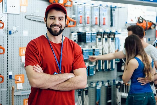 Il commesso sta posando nel negozio degli attrezzi elettrici Foto Premium