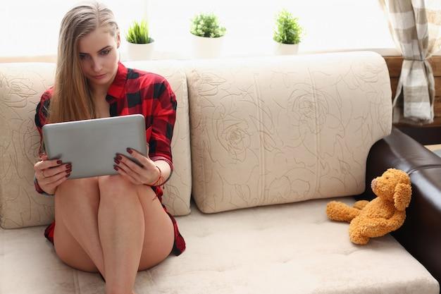 Il computer portatile della tenuta della donna in armi si siede sul sofà Foto Premium