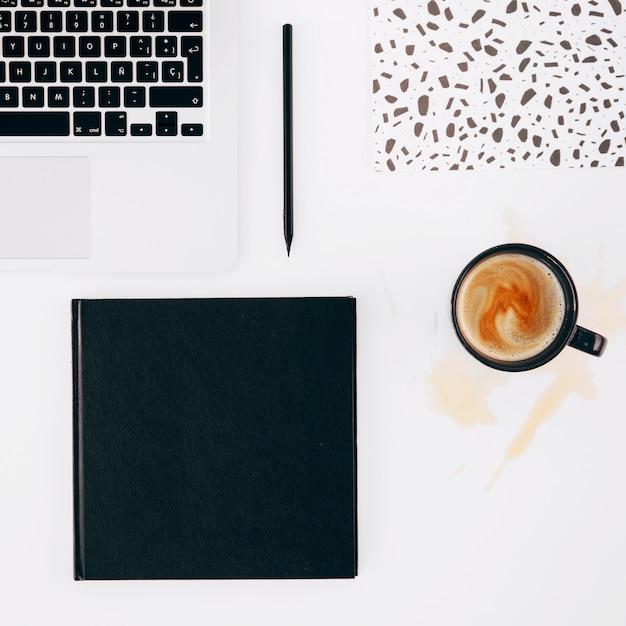Il computer portatile; matita; taccuino e tazza di caffè rovesciata su priorità bassa bianca Foto Gratuite