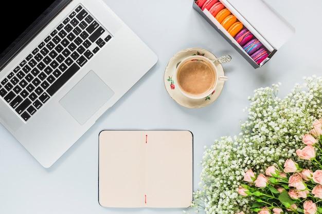 Il computer portatile; tazza di caffè; mazzo dei fiori e dei maccheroni su fondo bianco Foto Gratuite